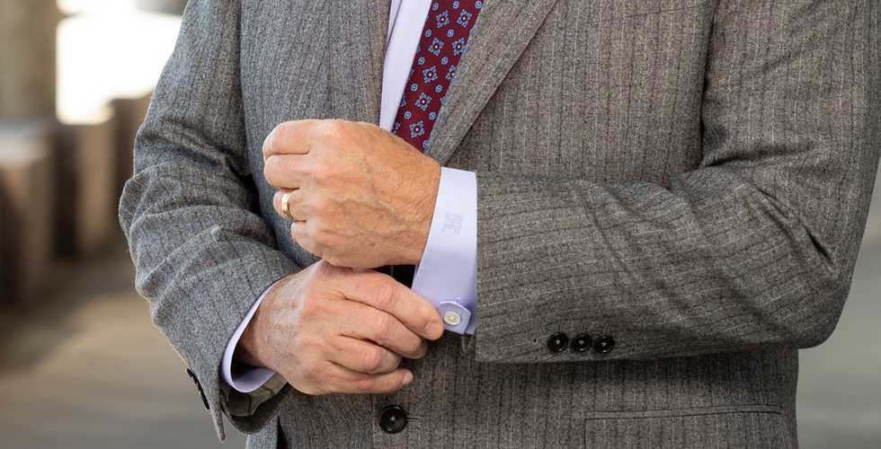 Man in gray pinstripe suit adjusting his shirt cuff