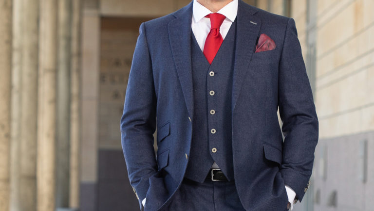 man with hands in pocket and blue suit